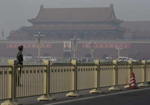 Paramilitary policemen guard and patrol on Tiananmen Square, near Tiananmen Gate, back, where state media says a sports-utility vehicle veered through a crowd and crashed into a stone bridge / AP