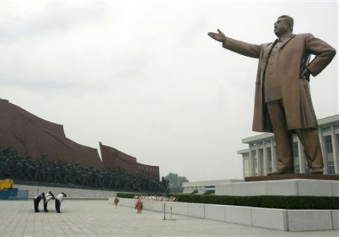 North Koreans bow before a statue of Kim Il Sung, the regime's founder. / AP