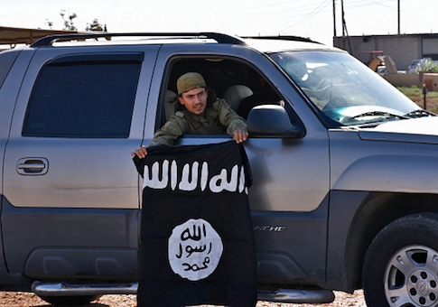 A member of the Syrian pro-government forces holds an Islamic State (IS) group flag after they entered the village of Dibsiafnan on the western outskirts of the Islamist's Syrian bastion of Raqqa