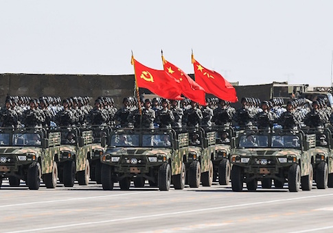 Chinese soldiers carry the flags of the Communist Party, the state, and the People's Liberation Army during a military parade
