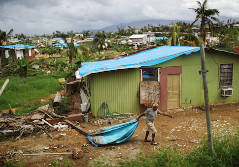 A local resident cleans debris near his damaged home in an area without electricity in San Isidro, Puerto Rico