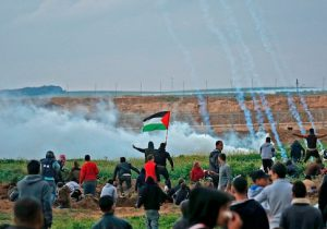 Palestinians run through tear gas fumes during clashes following a demonstration along the border with Israel east of Gaza City