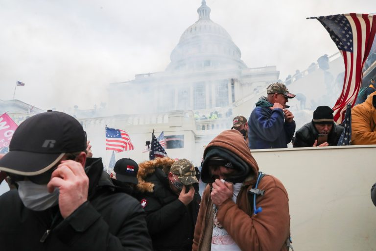 Supporters of U.S. President Donald Trump cover their faces to protect from tear gas during a clash with police officers in front of the U.S. Capitol Building